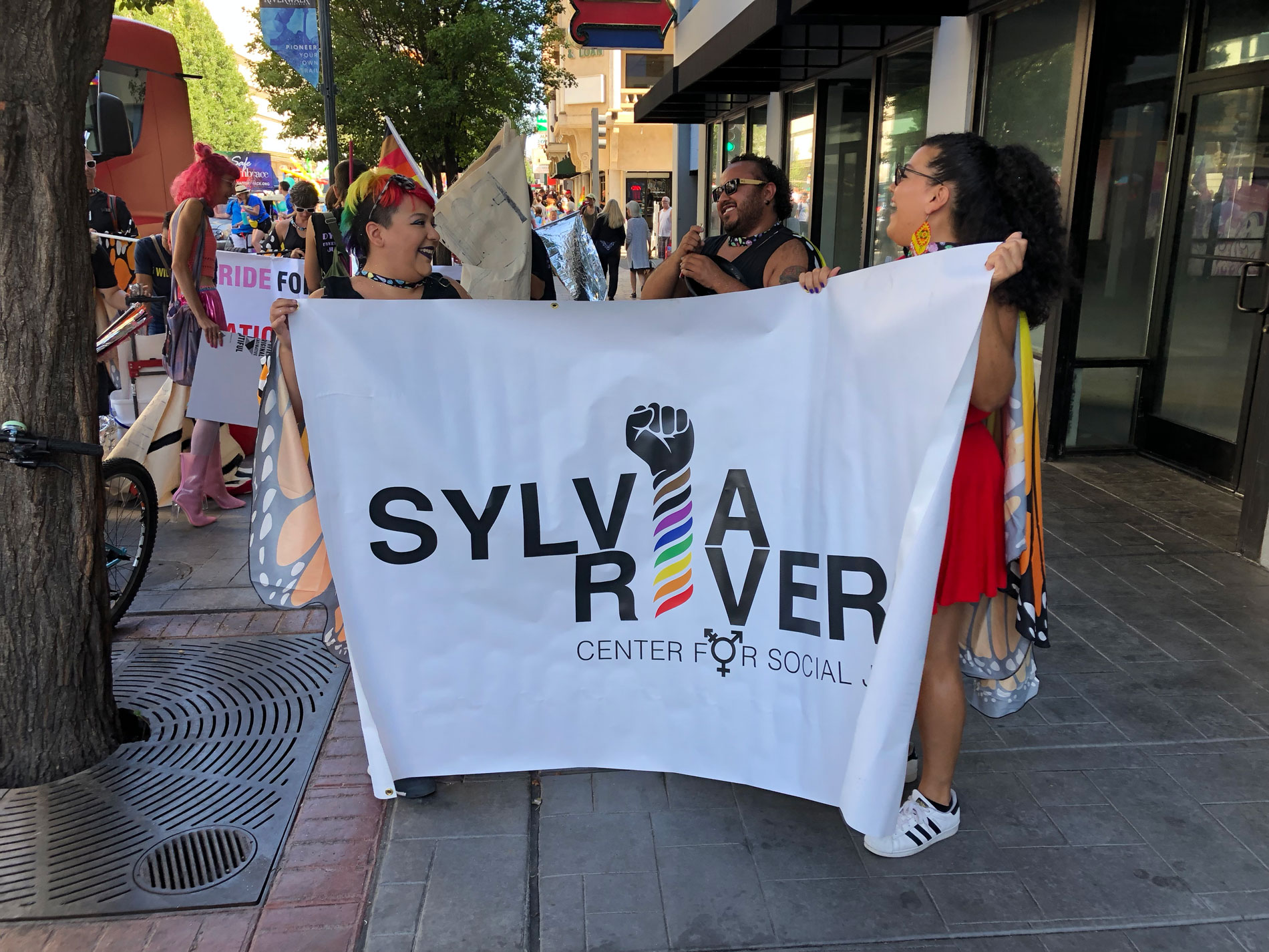 Members of the Sylvia Rivera Center for Social Justice (SRC) holding up their organization's banner during Pride