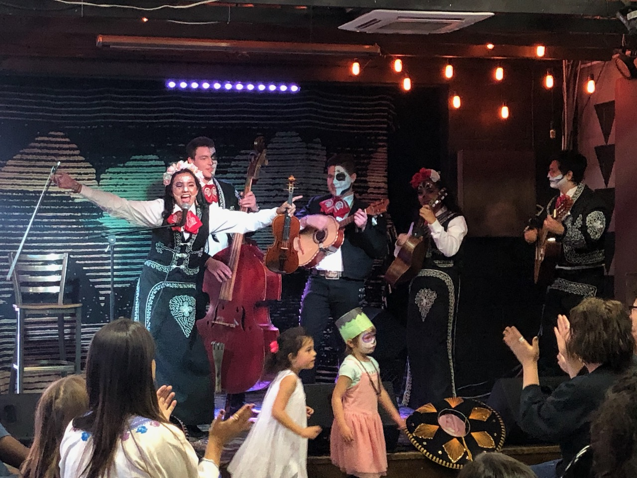 Young mariachi band performing in front of an all-ages audience during Día de los Muertos celebration