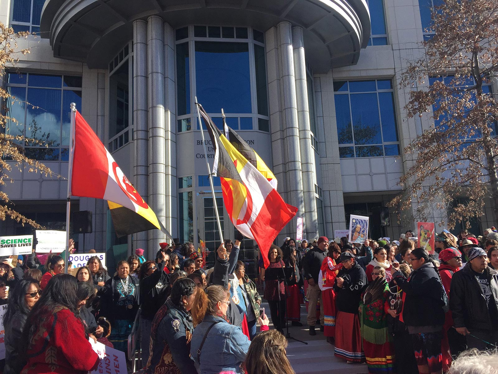 Indigenous protestors assembled in front of a federal court house listening to individuals speaks
